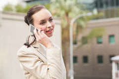 Young businesswoman talking on phone. Outside in the city Stock Image