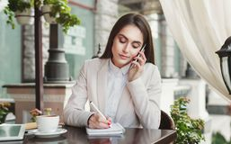 Young businesswoman talking on smartphone and making notes in notebook Royalty Free Stock Photo