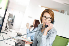 Young businesswoman talking on telephone at desk in office royalty free stock photos