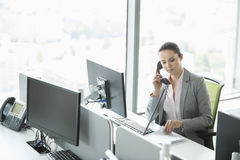Young businesswoman talking on telephone in office Stock Images