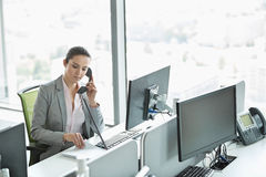Young businesswoman talking on telephone in office Royalty Free Stock Photo