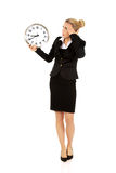 Young businesswoman terrified looks at the clock Stock Photos