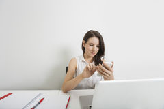 Young businesswoman text messaging through cell phone at desk in office Royalty Free Stock Image