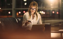 Woman working late in office. Young businesswoman texting on mobile phone while working on laptop late in office. Female executive working late in office royalty free stock photo