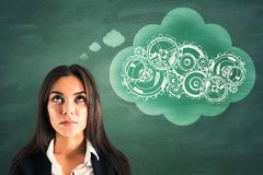 Businesswoman thinking about cogs. Young businesswoman thinking about cogs on chalkboard background. Industry and mechanism concept stock photography