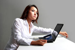 Young businesswoman thinking in front of laptop. A portrait of  a young businesswoman thinking in front of laptop Royalty Free Stock Photo