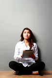 Young businesswoman thinking while holding on a tablet Royalty Free Stock Image