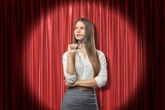 Young businesswoman thinking and looking away, holding glasses near lips, standing in spotlight near red stage curtain. royalty free stock photography