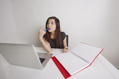 Young businesswoman. Thoughtful young businesswoman with diary and laptop at office desk stock photos