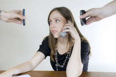 Young businesswoman with three cellphones Royalty Free Stock Photography