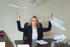 Young businesswoman throwing some paper sheets in her office. Young businesswoman throwing some paper sheets in her office Stock Image