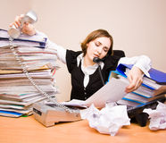 Young businesswoman with tons of documents. Calling phone royalty free stock photography