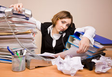 Young businesswoman with tons of documents. Young tired businesswoman with tons of documents calling phone Stock Photos