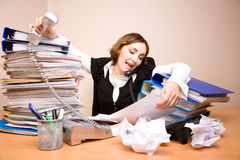 Young businesswoman with tons of documents. Calling phone royalty free stock photos