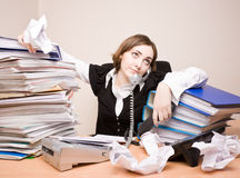 Young businesswoman with tons of documents. Calling phone Stock Photography