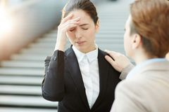 Forgot it. Young businesswoman touching her head and expressing that she forgot something while colleague saying it is okay Royalty Free Stock Photos