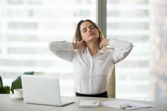Businesswoman taking work break doing office exercises massaging. Young businesswoman touching massaging stiff neck after sedentary computer work in incorrect royalty free stock photo
