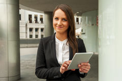 Young businesswoman touching tablet in the city. Smiling. Stock Photography