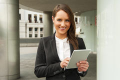 Young businesswoman touching tablet in the city. Smiling. Stock Images