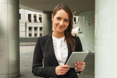 Young businesswoman touching tablet in the city. Smiling. Royalty Free Stock Photo