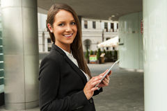 Young businesswoman touching tablet in the city. Smiling. Stock Image