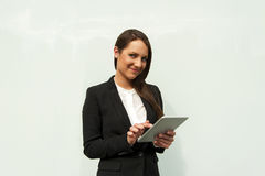 Young businesswoman touching tablet by the wall in the city. Stock Image