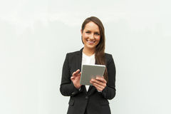 Young businesswoman touching tablet by the wall in the city. Royalty Free Stock Photo