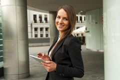 Young businesswoman touching tablet by the wall in the city. Royalty Free Stock Images