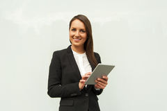 Young businesswoman touching tablet by the wall in the city. Stock Photo