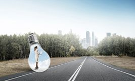 Businesswoman inside light bulb stock photography