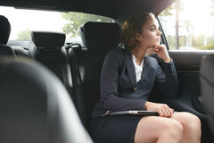Young businesswoman traveling to work in the luxury car Stock Photos