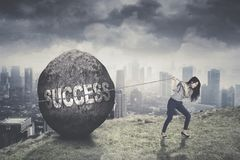 Young businesswoman trying to pull success word. Picture of young businesswoman trying to pull success word in a stone on the mountain Stock Photography