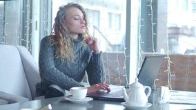 Young businesswoman typing on keyboard notebook sitting at couch in cafe with tea cup. Beautiful woman using laptop for. Work during business lunch in modern stock video