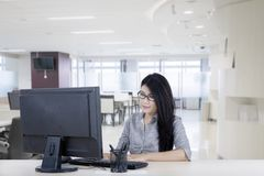 Young businesswoman typing on a keyboard. Picture of young businesswoman typing on a computer keyboard while sitting in the office Royalty Free Stock Image