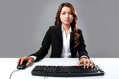 Young businesswoman typing on keyboard. A portrait of a young businesswoman typing on keyboard computer Royalty Free Stock Images