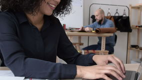 Young businesswoman typing on a laptop. Two colleagues working in a small studio stock footage