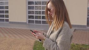 Adult luxury woman is sending sms by smartphone on street in city, spring day stock video