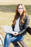 Young businesswoman use laptop sitting in the park Royalty Free Stock Photography