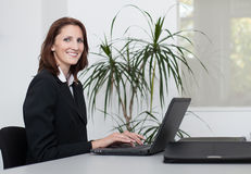 Young businesswoman uses a notebook. Young businesswoman works with a laptop in an office and smiles Stock Photography
