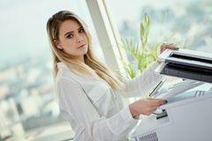 Young businesswoman uses a scanner in a skyscraper office. Beautiful young businesswoman poses in a sunny skyscraper office Stock Photo