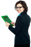 Young businesswoman using calculator. Bespectacled entrepreneur using calculator. Turning back and smiling royalty free illustration