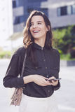 Young businesswoman using cell phone. On the street Royalty Free Stock Photo