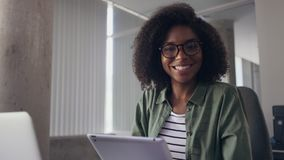 Young businesswoman using digital tablet looking at camera stock footage