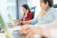 Young businesswoman using headset and laptop with colleagues in foreground at office.  Stock Photo