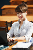Young business woman using laptop at sidewalk cafe Stock Images