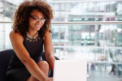 Young businesswoman using laptop computer in modern interior stock photo