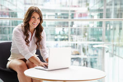Young businesswoman using laptop computer in modern interior Stock Photography