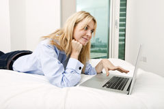 Young businesswoman using laptop while lying in bed Royalty Free Stock Image