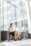 Young businesswoman using laptop at office lobby Royalty Free Stock Image