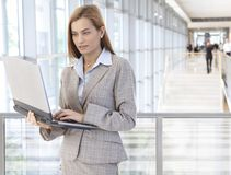 Businesswoman using laptop in office lobby Stock Photos